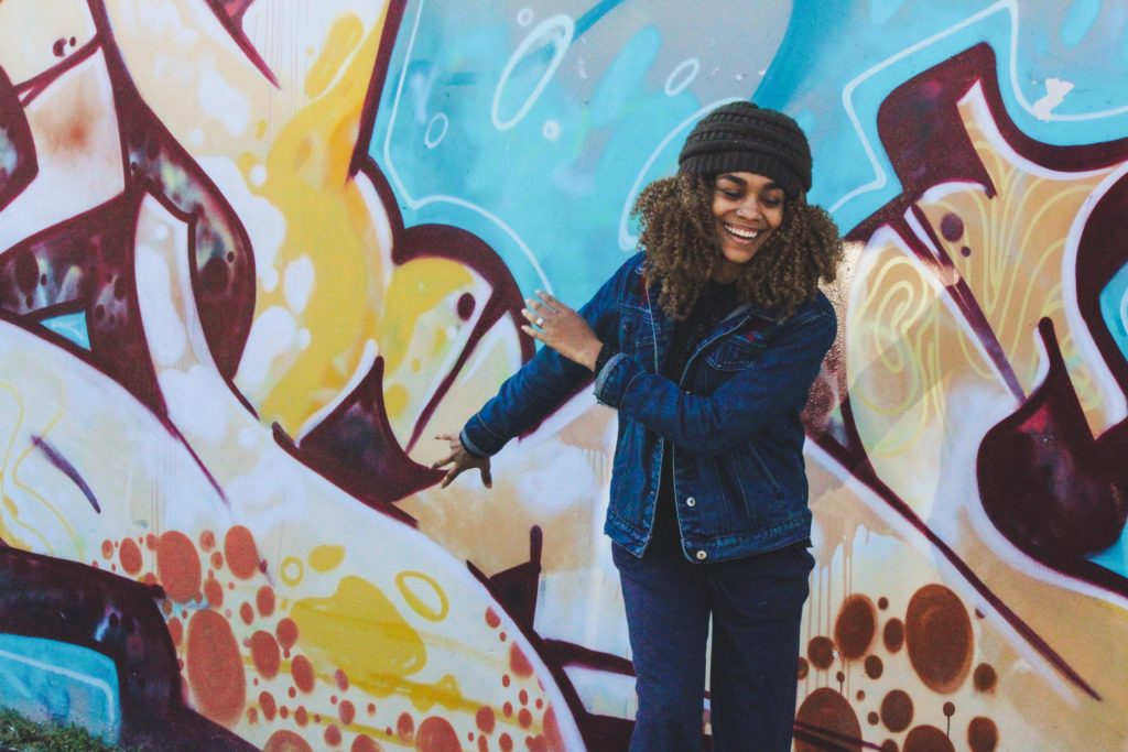 woman happy in front of mural wall with covid fatigue strategies
